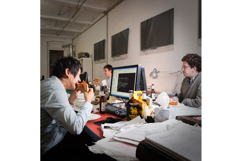 Yohan Kim, an architect, worked over time with his coworkers.  They had pizza and beer on the desk. Age: 28  Time: 7:27 PM    Location: Dumbo, Brooklyn