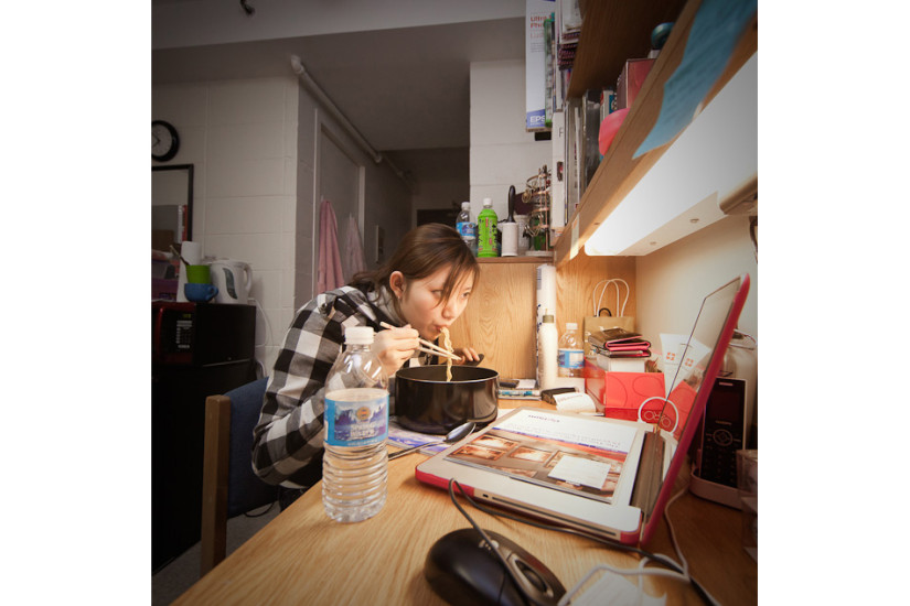 Jai Yoon Lee, a student from South Korea has dinner in her dorm room watching her favorite Japanese TV shows. Age: 20   Time: 7:51 PM    Location: Greenwich Village, New York